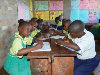 school children in class writing in a lesson