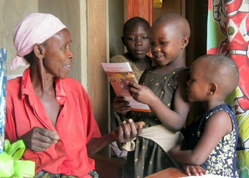 A grandmother and her grandchildren in Bushenyi District Uganda read an Uwezo report on learning outcomes. Courtesy Photo/Uwezo.