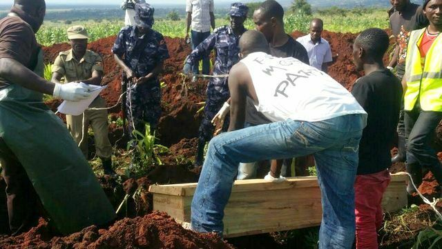 Police burying one of the bodies of the Kasese attack last year