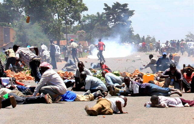 People take cover during a demonstration. File Photo