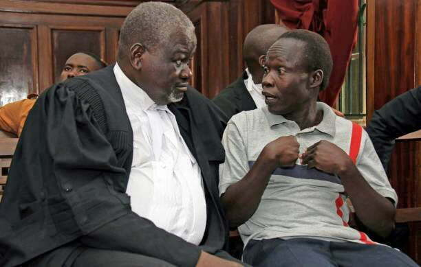 Suspected LRA (Lords Resistance Army) member Thomas Kwoyelo (R) talks with his lawyer Charles Dalton Opwonya (L) during a pre-trial session at the High Court in Kampala on February 1, 2017.