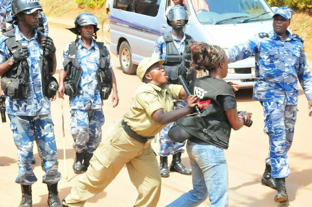 A police officer pushing a journalist as she tried to cover a protestors during the closure of Daily Monitor in 2013
