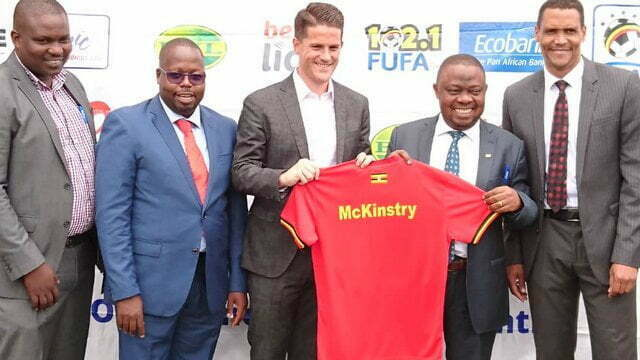 Jonathan Mckinstry (center) is handed a Cranes Jersey by FUFA President Justus Mugisha (second-right) at FUFA House in Mengo