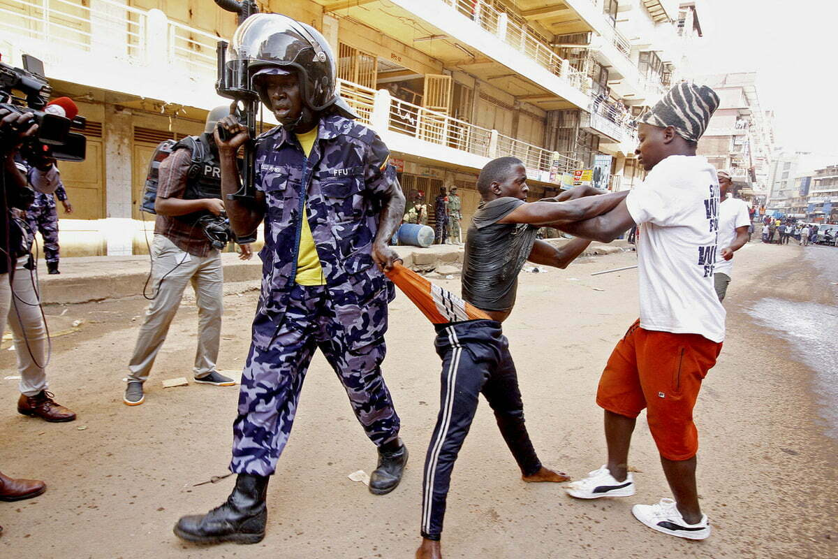 Armed security officer drags a young man by his boxers