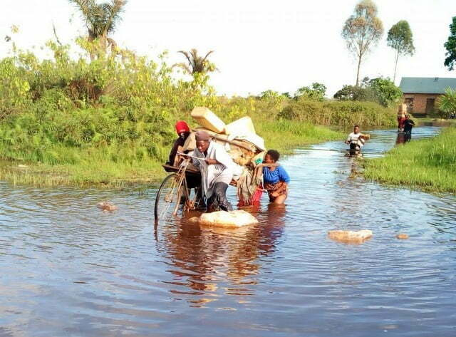 A family using a bicycle to run away from the flood that has cut off landing sites in Masaka district