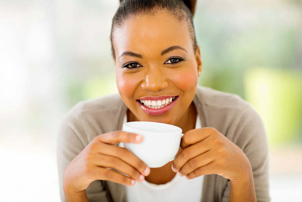 happy african woman drinking tea in the morning at home