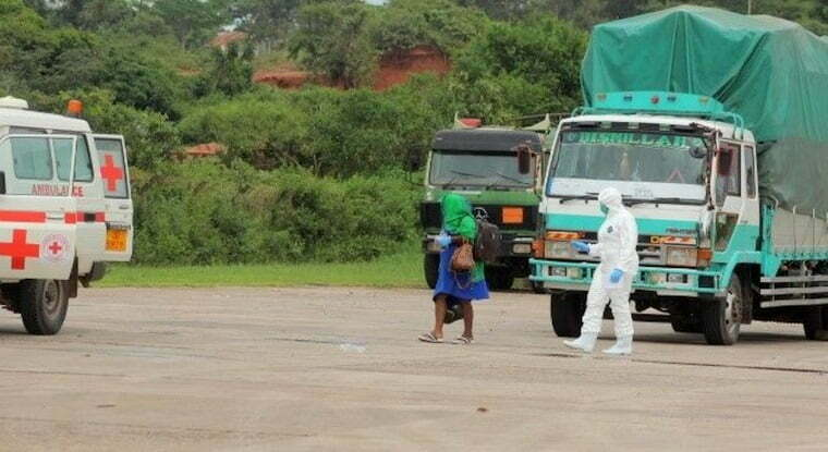 Medical worker leading a woman who come into contact with covid-19 positive truck driver