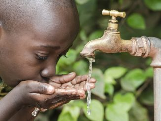 Black Boy Drinking from a Water Tap