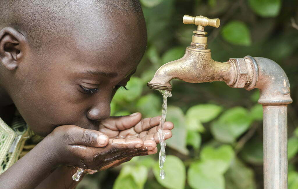 Proud Black Boy Drinking from a Water Tap