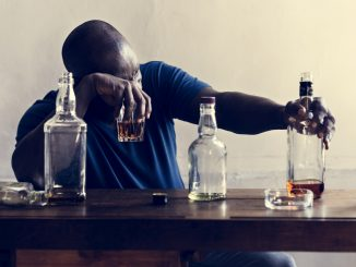 African descent man sitting drinking whiskey alcoholic addiction bad habit