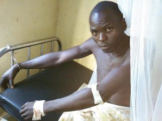 Ibrahim Damba handcuffed on his hospital bed