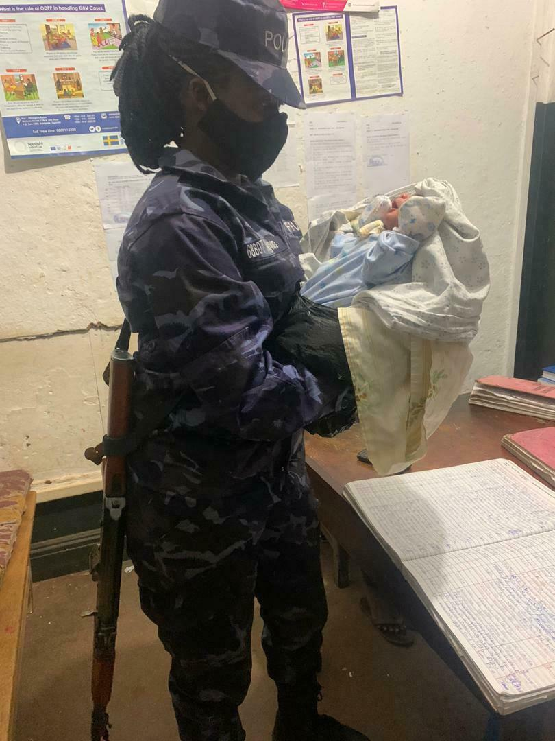 A female officer with the abandoned baby at Kampala Central Police Station